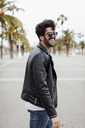 Spain, Barcelona, happy young man on promenade with palms - MAUF01574