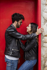 Happy young couple standing at red door - MAUF01577