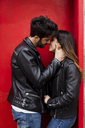 Affectionate young couple kissing at red door - MAUF01580