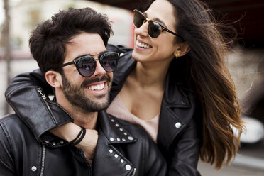 Portrait of happy young couple wearing sunglasses and leather jackets - MAUF01586
