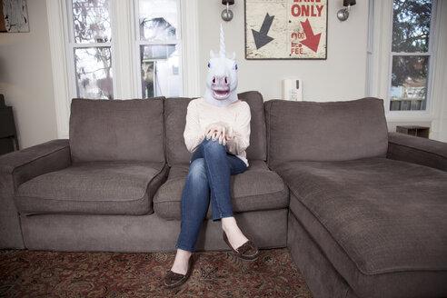 Girl sitting on sofa wearing unicorn head mask - ISF18645