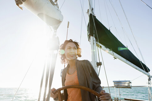 Young woman steering yacht - ISF18705
