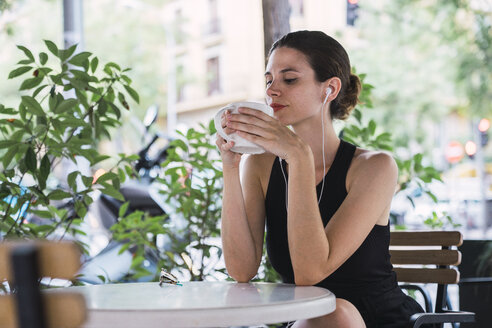 Young businesswoman sitting in coffee shop, taking a break, drinking tea - KKAF01246