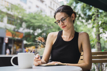 Young woman sitting in coffee shop, brainstorming, writing notes in notebook - KKAF01258