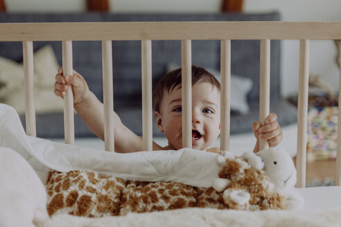 Baby boy holding on to his cot laughing - JLOF00124
