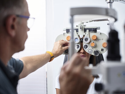 Optometrist examining young woman's eye - CVF01032