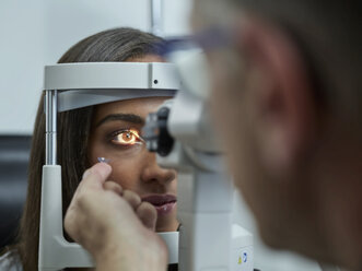 Optometrist examining young woman's eye, contact lens on index finger - CVF01035