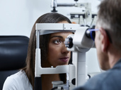 Optometrist examining young woman's eye - CVF01038