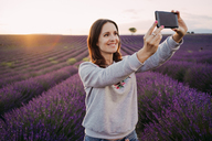 France, Valensole, portrait of smiling woman taking selfie in front of lavender field at sunset - GEMF02222