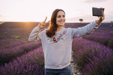 France, Valensole, portrait of smiling woman taking selfie in front of lavender field at sunset - GEMF02225