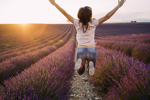 France, Valensole, back view of happy woman jumping in the air in front of lavender field at sunset - GEMF02231