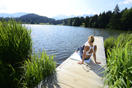 Germany, Mittenwald, back view of woman relaxing on jetty at lake - ECPF00233