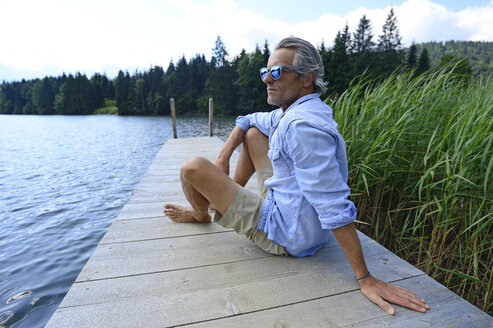 Germany, Mittenwald, mature man relaxing on jetty at lake - ECPF00242