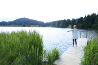 Germany, Mittenwald, back view of woman standing with arms outstretched on jetty at lake - ECPF00245