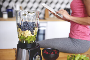Young woman using tablet in the kitchen while preparing smoothie - ABIF00785
