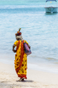 Mauritius, Trau-aux-Biches, local woman wearing sari and with ananas on the head walking at the beach - MMAF00440