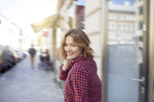 Portrait of smiling woman in the city - PNEF00786