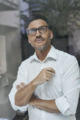 Portrait of man with stubble behind windowpane wearing white shirt and glasses - PNEF00822