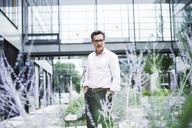 Portrait of confident businessman outside office building - UUF14667