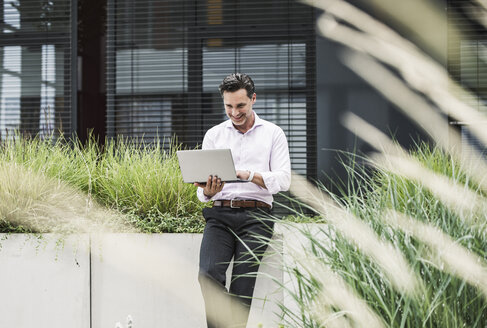 Smiling businessman using laptop outside office building - UUF14685
