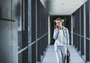 Businesswoman on cell phone walking in office passageway - UUF14697