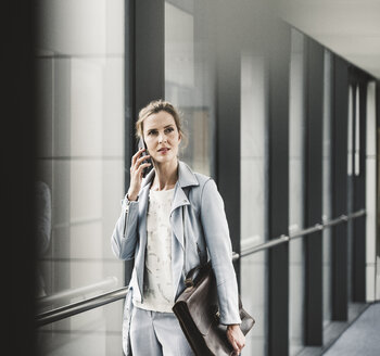 Businesswoman on cell phone at the window in office passageway - UUF14700