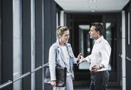 Businesswoman and businessman arguing in office passageway - UUF14703