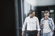 Businesswoman and businessman talking in office passageway - UUF14706