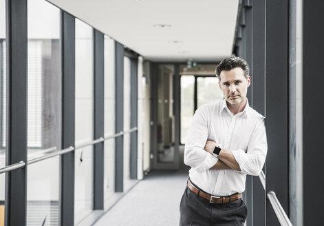 Portrait of confident businessman in office passageway - UUF14724