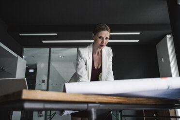 Businesswoman in office working on plan at desk - UUF14763