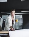Businesswoman in office working on plan at desk - UUF14766