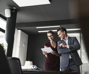 Businesswoman and businessman sharing tablet in office - UUF14778