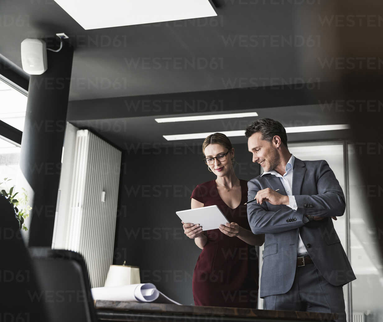 Businesswoman and businessman sharing tablet in office - UUF14778 - Uwe Umstätter/Westend61