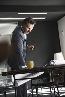Businessman in office looking at plan on desk - UUF14784