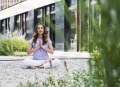 Woman practicing yoga in garden outsde office building - UUF14787