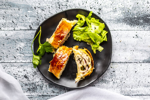 Swiss roll, puff pastry with sausage meat, cheese, onion, parsley and salad on plate - SARF03866