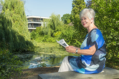 Portrait of smiling senior woman sitting at lake with newspaper - FRF00702
