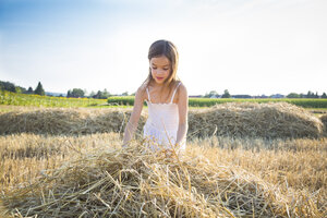 Little girl standing in havested field - LVF07354
