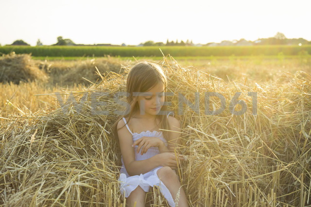 Little girl sitting on straw of havested field - LVF07357