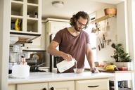 Man preparing muesli in his kitchen - MFRF01151