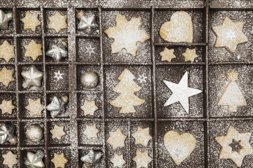 Homemade Christmas cookies, stars and Christmas baubles in old wooden typecase - GWF05615