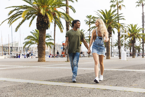 Spain, Barcelona, multicultural young couple walking hand in hand on promenade - WPEF00719