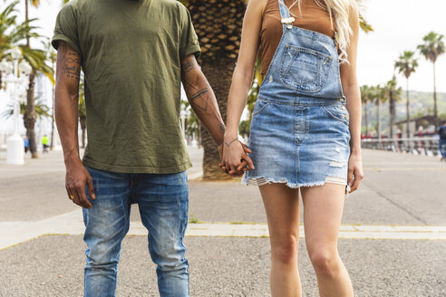 Spain, Barcelona, multicultural young couple holding hands on promenade, partial view - WPEF00725