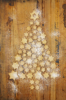 Star-shaped biscuits forming Christmas Tree on wooden  background - GWF05617