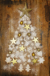 Christmas cookies and golden Christmas baubles and stars forming Christmas Tree on wood - GWF05620