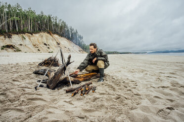 Man collecting firewood on the beach, preparing campfire - VPIF00410