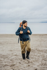 Man with backpack, walking on the beach - VPIF00413