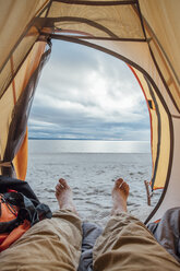 Feet of man, lying in tent on beach - VPIF00416