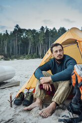 Backpacker sitting in front of his tent on the beach - VPIF00422