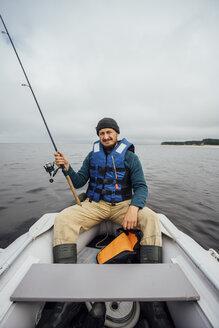 Man sitting on boat fishing with fishing rod - VPIF00431